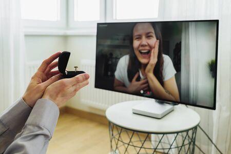 オンラインビデオ通話を使用してガールフレンドにプロポーズをする男性。幸せな女性に指輪を見せる 写真素材
