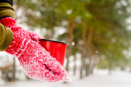 Red mug with hot coffee or tea drink on snow in winter. Red knitted mittens on hands
