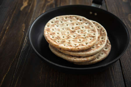 Stack of soft flatbread in pan on wooden table