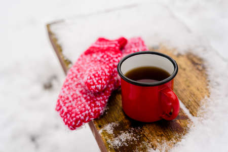 Red mug with hot coffee or tea drink on snow in winter. Red knitted mittens on table