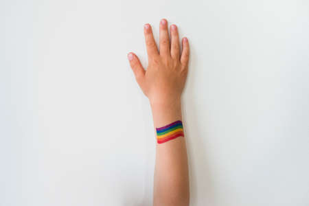 Rised child hand with rainbow LGBTQ pride flag tattoo. Movement symbol