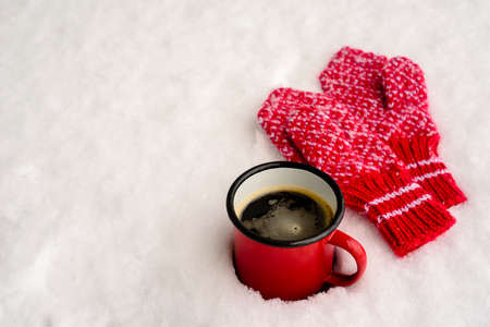 Red mug with hot coffee or tea drink on snow in winter. Red knitted mittens