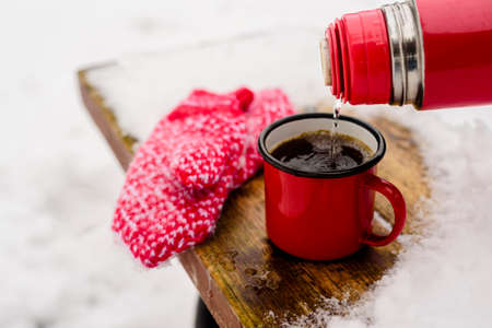 Red mug with hot coffee or tea drink on snow in winter. Red knitted mittens and thermos on table