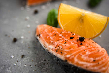 Salmon fillet piece with lemon, salt, black pepper and basil on gray 免版税图像
