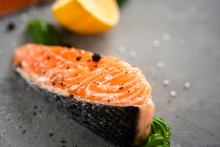 Salmon fillet piece with lemon, salt, black pepper and basil on gray Standard-Bild - 151206371
