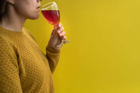 Woman in yellow sweater drinking glass of wine in hand