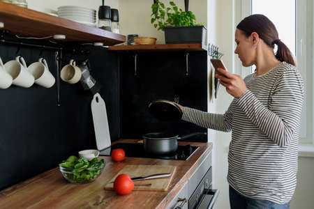 Woman using phone while cooking healthy food in kitchen