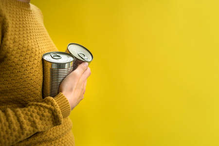 Woman holding steel can in hand. Canned food concept. Yellow sweater and background