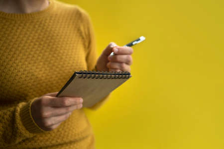 Woman Writing by left hand in notepad. Left hander day concept. In yellow sweater Standard-Bild - 151554116