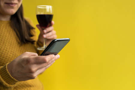 Woman in yellow sweater using phone and holding glass of red wine