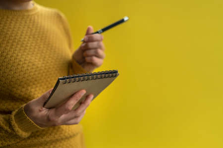 Woman Writing by left hand in notepad. Left hander day concept. In yellow sweater