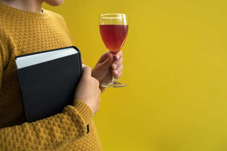 Woman in yellow sweater holding book and glass of wine