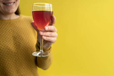Woman in yellow sweater holding glass of wine in hand
