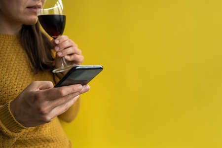 Woman in yellow sweater using phone and drinking glass of red wine