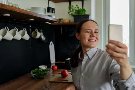 Woman taking pictures of herself on phone in kitchen