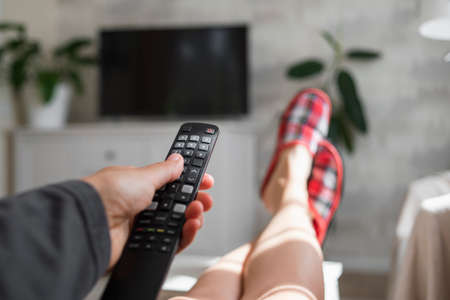 Hand with TV remote control in living room. Watching television. Legs in slippers Banco de Imagens