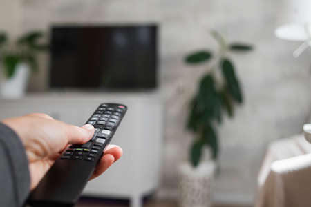 Hand with TV remote control in living room. Watching television