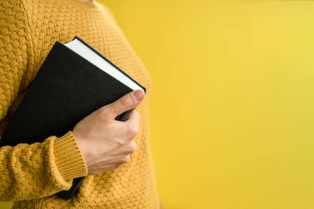 Woman student in sweater with books on yellow Standard-Bild
