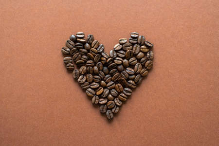 Heart-shaped coffee beans on brown background close up, flat lay