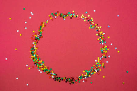 Christmas wreath from star sparkles on red background