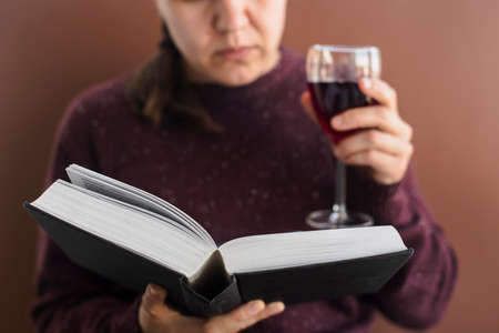 Woman in brown sweater holding book and glass of wine Standard-Bild