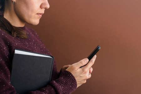 Woman in brown sweater using smartphone. Holding book