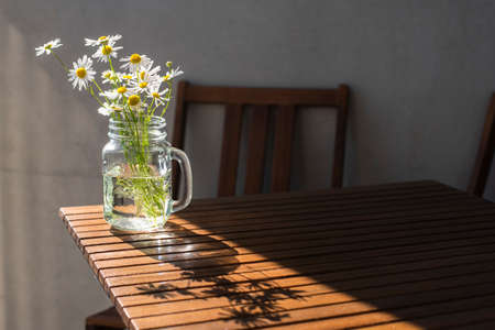 Bouquet of wild daisies in glass jar on wooden table at sunny day