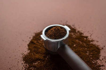 Portafilter coffee machine holder with ground beans on brown Standard-Bild