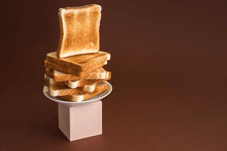 Heap of toasts on pedestal on brown. Modern still life, breakfast