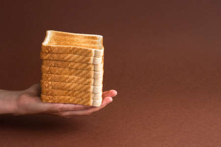 Heap of toasts in hand on brown. Breakfast concept
