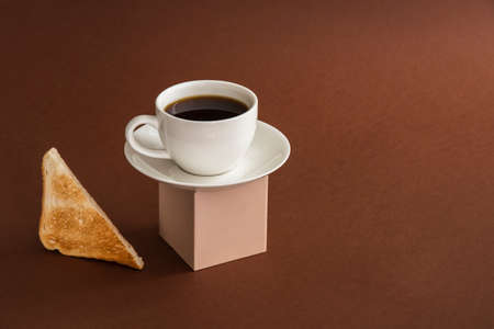 Cup of coffee on cube pedestal with toasts on brown. Modern still life, breakfast