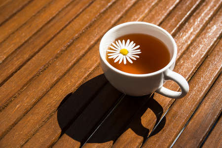 Cup of herbal chamomile tea on wooden table at sunny day Standard-Bild