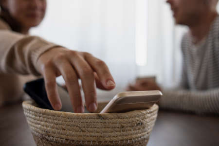 People on meeting without their phones. Digital detox concept. Turned off phones putting in basket