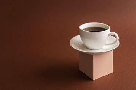 Cup of coffee on cube pedestal on brown. Modern still life Standard-Bild