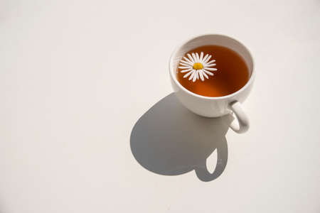 Cup of herbal chamomile tea on white table at sunny day