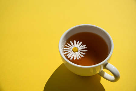 Cup of herbal chamomile tea on yellow at sunny day