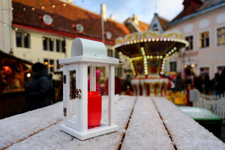 Lantern with candle on wooden table in winter Christmas market in Tallinn