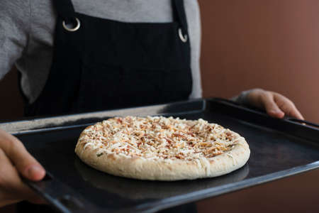 Woman in apron holding oven tray with frozen pizza