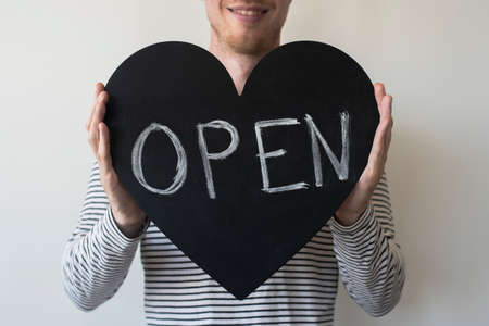 Man with OPEN heart shaped sign. Local business reopening