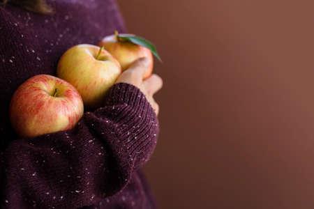 Happy woman gardener in brown sweater holding fresh apples