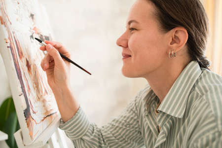 Woman in shirt drawing picture at easel at home. Sunny day Standard-Bild