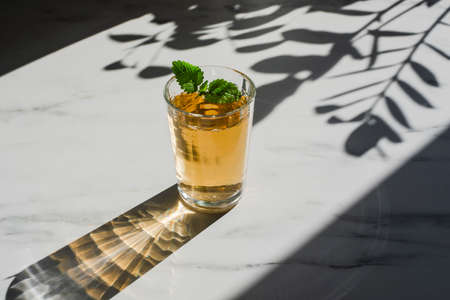 Glass of herbal mint tea at marble table with hard sun lught and plant shadows