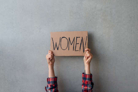 Woman activist hands with poster near concrete wall on street. For women rights Standard-Bild