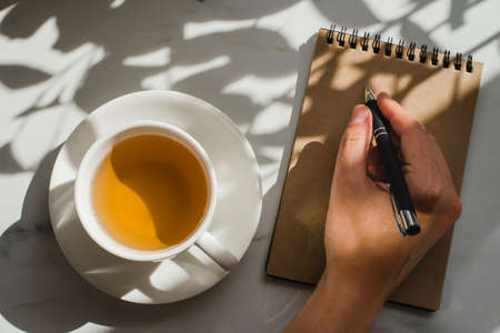 Cup of herbal green tea at marble table with notebook. Hard sun lught and plant shadows