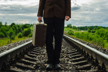 Man hipster with old retro suitcase on railway in country