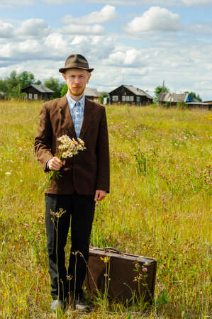 Man hipster with old retro suitcase and wildflowers bouquet in country. Cottagecore