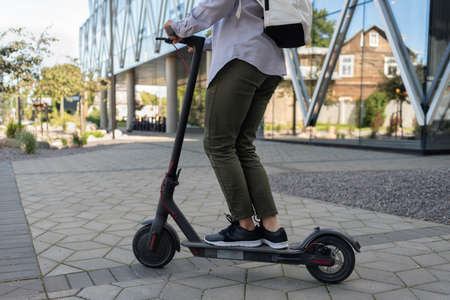 Woman riding at work on electric kick scooter near office building