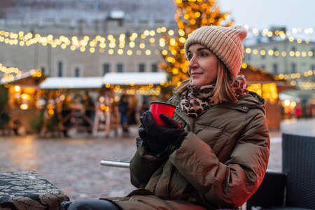 Woman drinking hot beverage or mulled wine from own mug on Christmas market in Tallinn