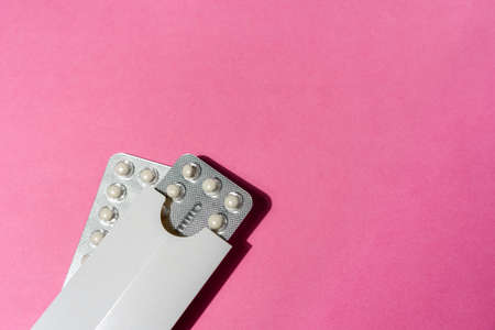 Birth control pills in everyday use case on pink