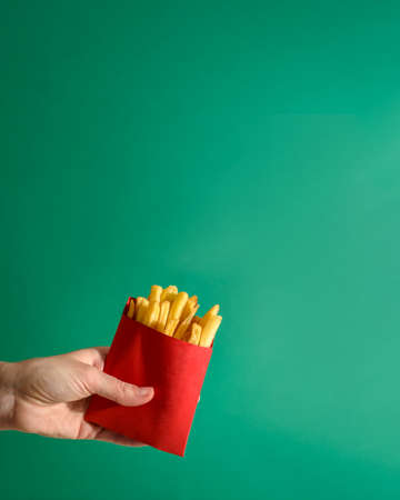 Fries potatoes in red package in hand on green background. Fast food